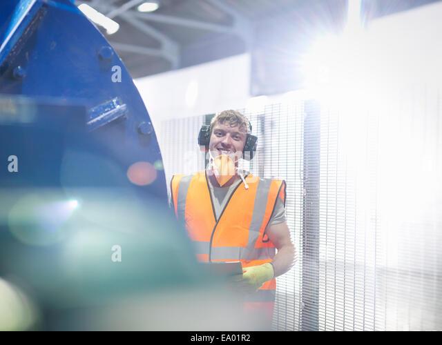 Worker in metal ore grinding mill - Stock-Bilder