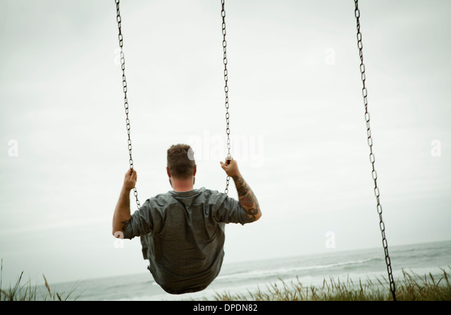 Mid adult man on beach swing - Stock Image