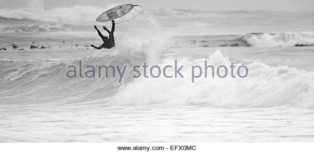 Surfer falling off surfboard on wave - Stock-Bilder