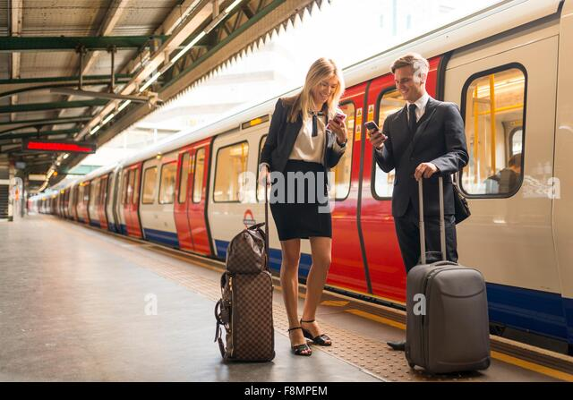 Businessman and businesswoman texting on platform, Underground station, London, UK - Stock Image