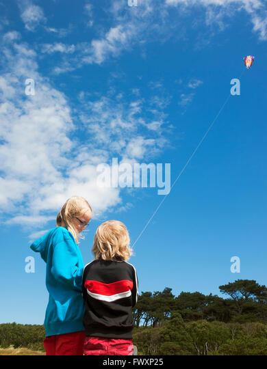 Sweden, Skane, Nyhamnslage, Two sisters (6-7, 10-11) flying kite - Stock Image