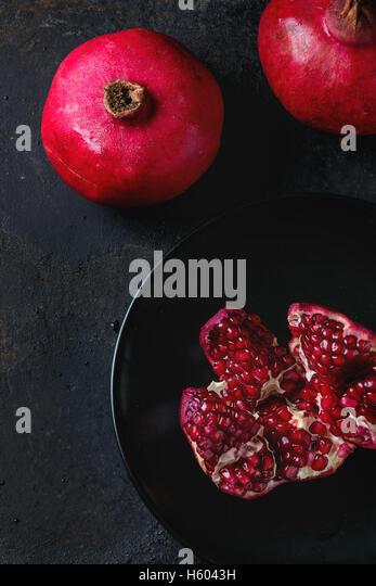 Slice and whole pomegranates - Stock Image