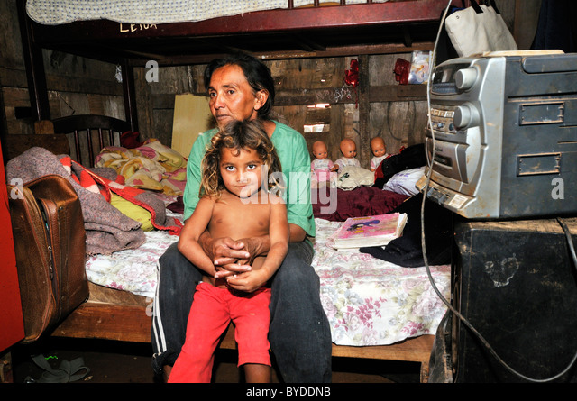 Mother, 43, and daughter, 8, sitting on a bed in their humble shack in a Favela or shanty town, the family lives - Stock Image