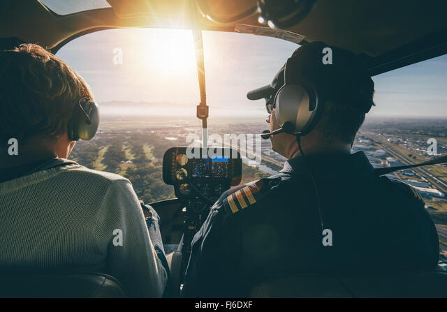 Inside view of a helicopter in flight, with man and woman pilots flying a helicopter on a sunny day. - Stock Image