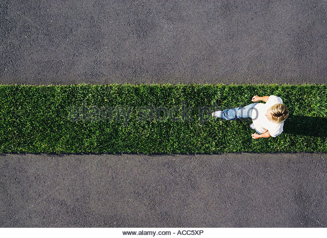 Woman walking on grass strip with pavement - Stock Image