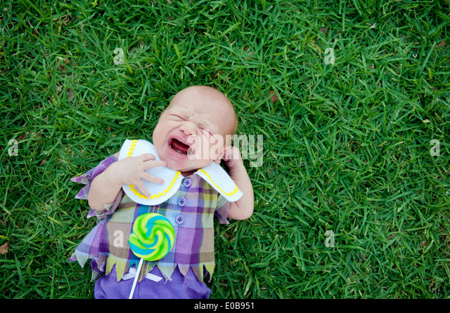Baby lying on grass, crying - Stock Image