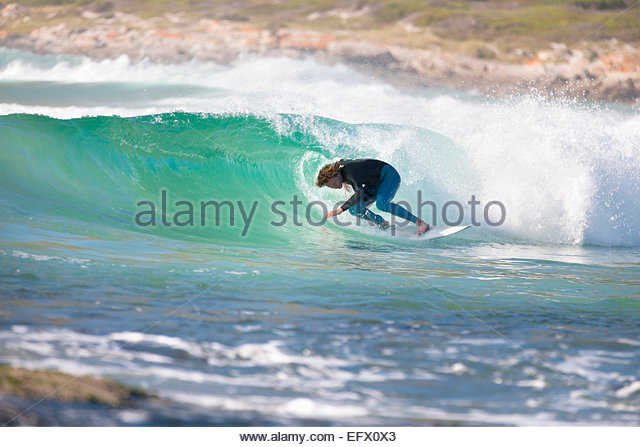 Surfer surfing in tunnel of large wave - Stock Image