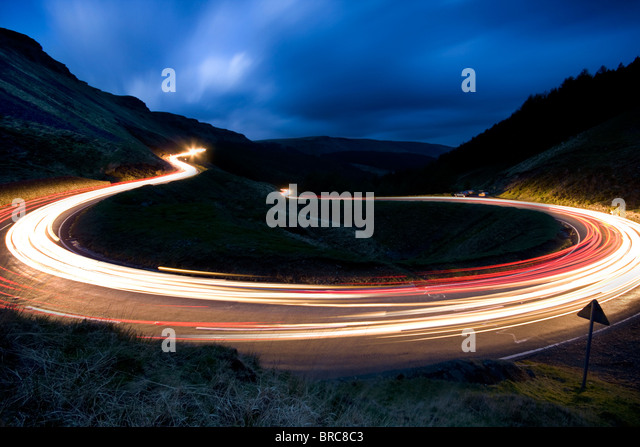 Car headlights trailing around a hairpin bend on a mounatin pass in South Wales. - Stock-Bilder