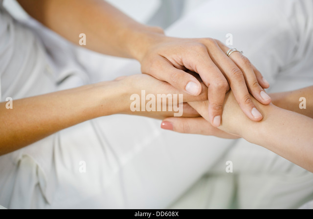 Doctor's Visit, Holding Hands, Close-up - Stock Image