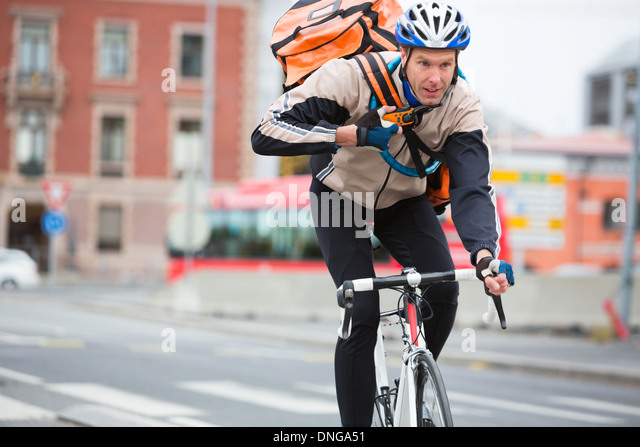 Male Cyclist With Courier Delivery Bag Riding Bicycle - Stock-Bilder