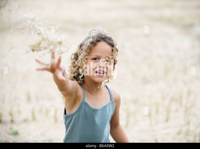 Young girl throwing wheat in field - Stock Image