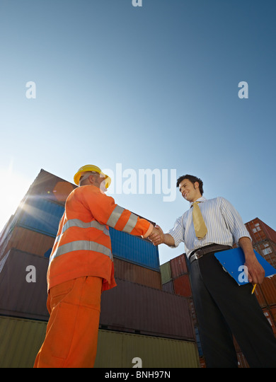 office worker and manual worker shaking hands near cargo containers - Stock Image