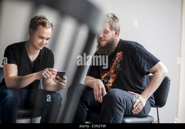 Businessmen using mobile phone in creative office - Stock Image