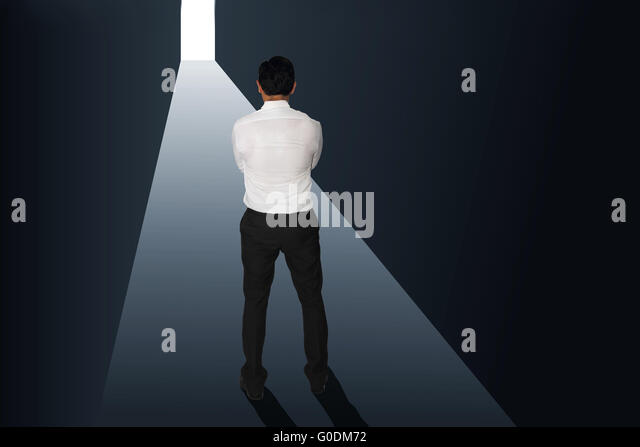 Challenge concept image rear view of a businessman starring at bright light at the end of dark tunnel - Stock Image