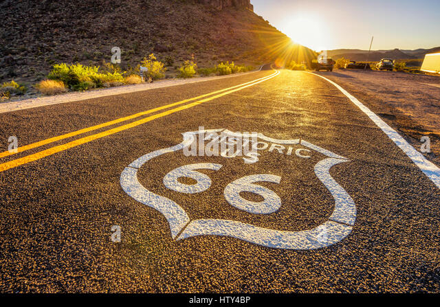 Street sign on historic route 66 in the Mojave desert photographed against the sun at sunset - Stock Image