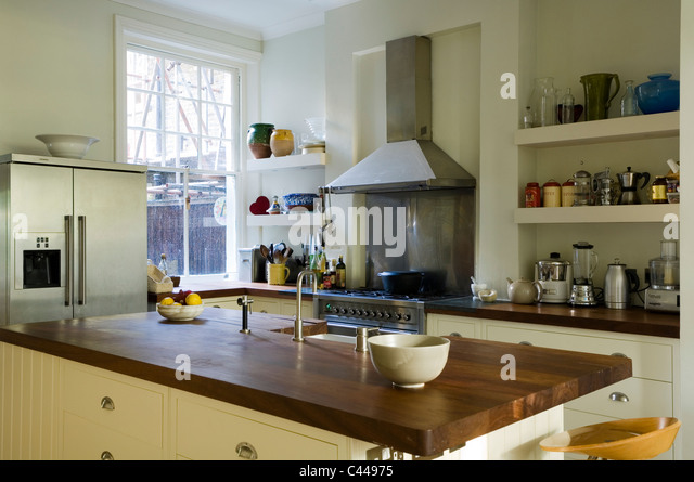 Iroko wood worktop on island in kitchen with open shelving - Stock Image