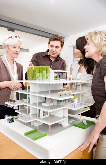 Team discussing architecture model - Stock Image