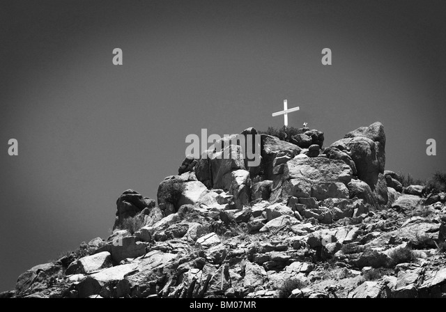 cross sits on top of a sandia mountain boulder mound landscape in black and white, along route 66, albuquerque, - Stock Image