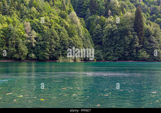 Scenery view of colorful mountain lake with green mountains - Stock Image