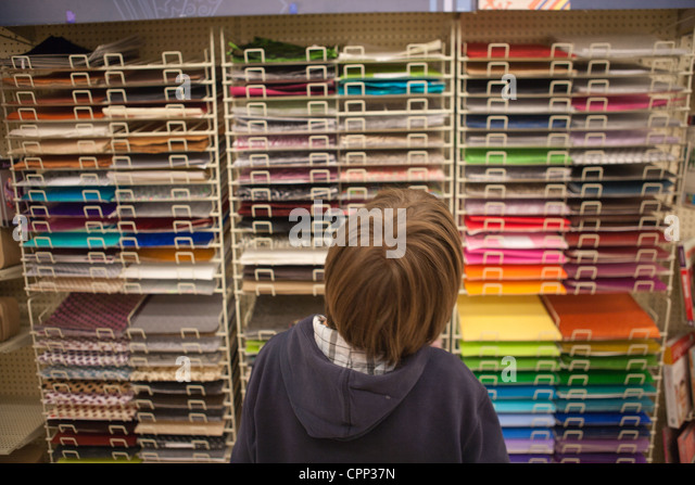 Nine year old boy looking at a selection of color paper in a craft store. - Stock Image