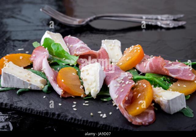 Salad with ham jamon serrano, camembert, arugula, melon on black stone slate plate on black background. Close up. - Stock Image