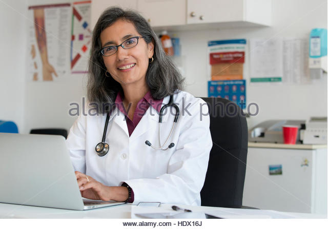Mixed Race doctor using laptop - Stock Image