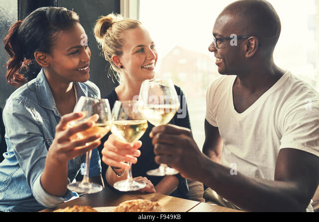 Ethnic friends at a bar drinking wine and eating tapas - Stock Image