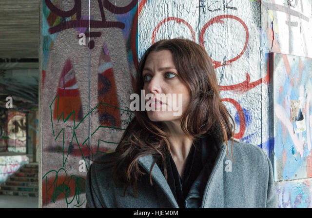 Attractive dark haired woman hiding behind a graffiti covered pillar - Stock Image
