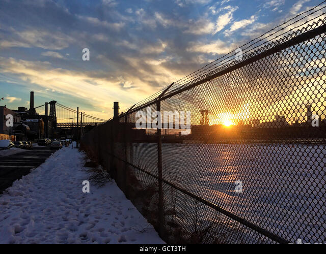 Landscape of Sunset and Williamsburg bridge viewed through chain link fence. - Stock Image