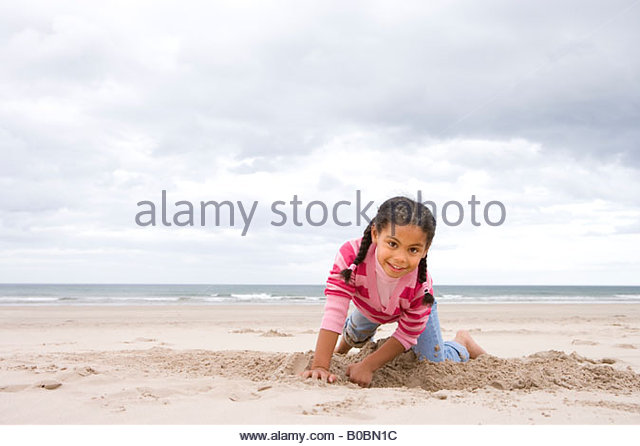 Girl  digging hole on beach, smiling, portrait - Stock Image