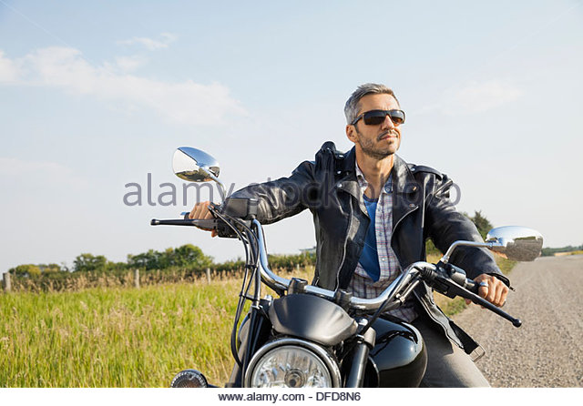 Male biker taking a break in the country during road trip - Stock Image