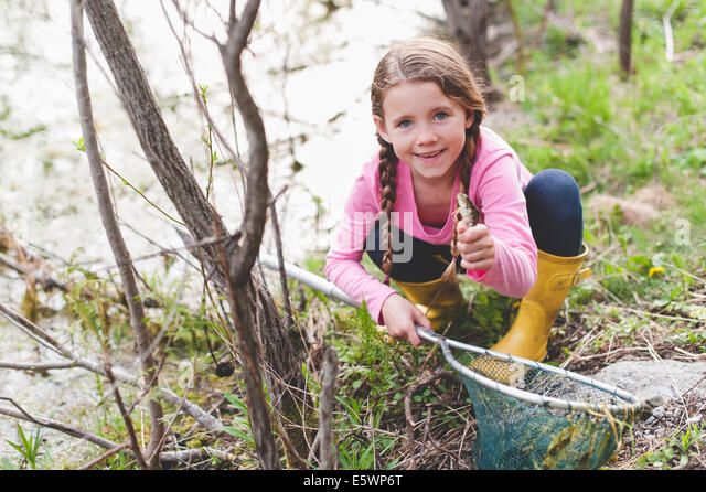 Portrait of girl holding up frog and fishing net - Stock Image