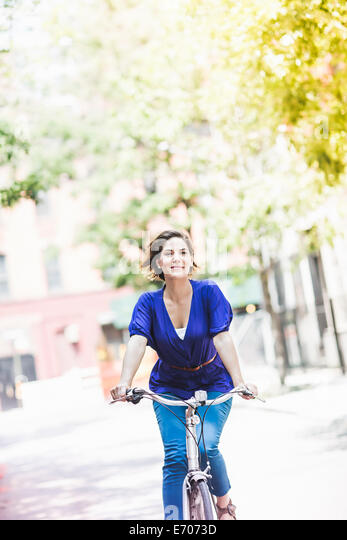 Mid adult woman cycling on city street, New York City, USA - Stock Image