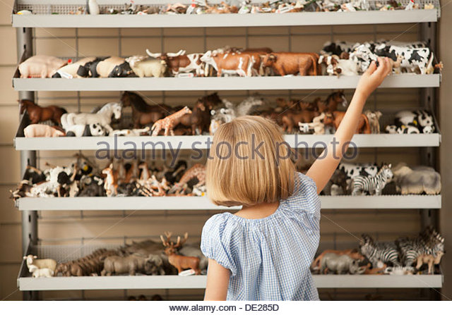 Girl reaching for plastic cow in toy store - Stock Image