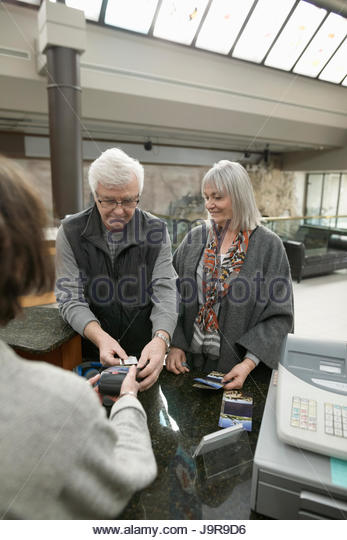 Senior couple paying entrance fee with credit card at museum cashier - Stock-Bilder