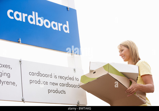 Man At Recycling Centre Disposing Of Cardboard - Stock Image