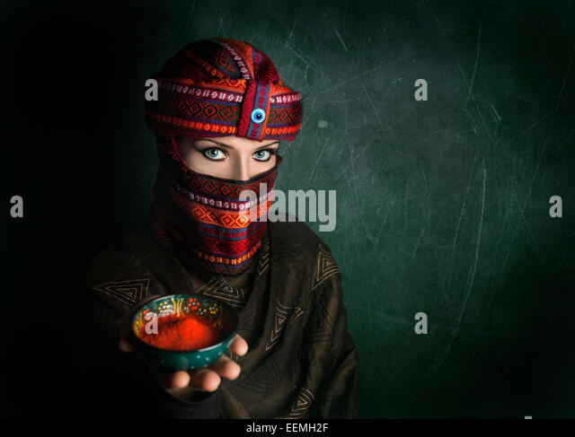Oriental woman in turban offering red chili powder at green textured wall - Stock Image