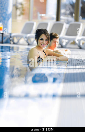 Couple in love relaxing by the side of the swimming pool - Stock Image