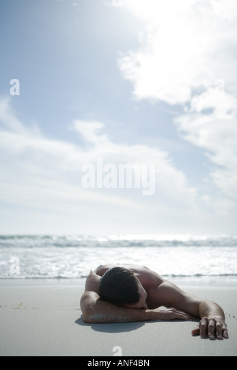 Man lying on beach - Stock Image