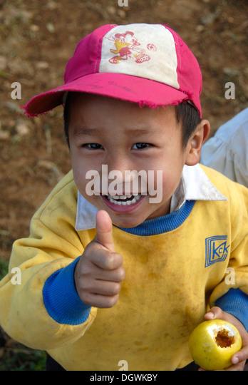 View from above, poverty, OK sign, thumbs up, grinning boy having fun, village of Ban Komaen, Phongsali district - Stock Image