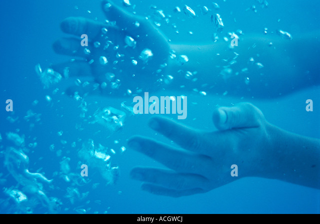 Hands of a woman underwater bubbles - Stock Image