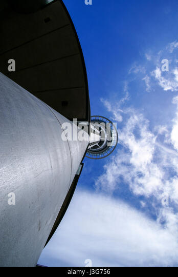 A view of the sky and clouds looking straight up the side of the Sky Tower. - Stock Image