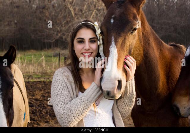 Argentina, Buenos Aires, Partido del Pilar, Manzanares, Portrait of teen (14-15) girl stroking horse - Stock Image