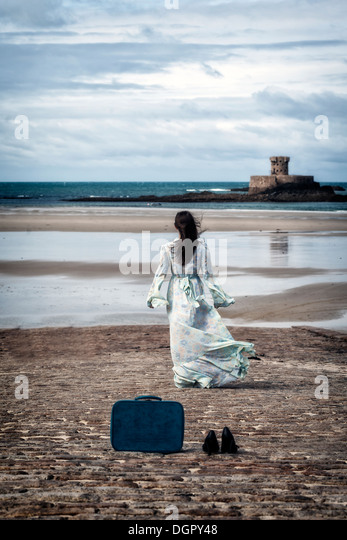 a woman in a floral dress is walking towards the sea, leaving her shoes and her suitcase behind her - Stock-Bilder
