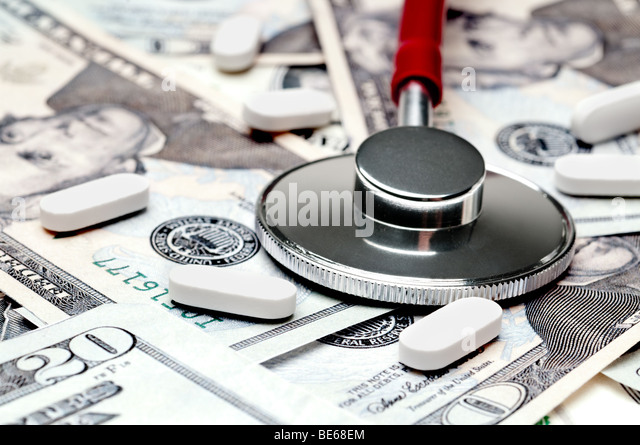 A horizontal image of a stethoscope and pills on American currency - Stock Image