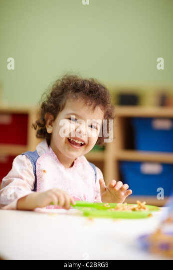 hispanic female preschooler eating pasta and smiling at camera. Vertical shape, waist up, copy space - Stock Image