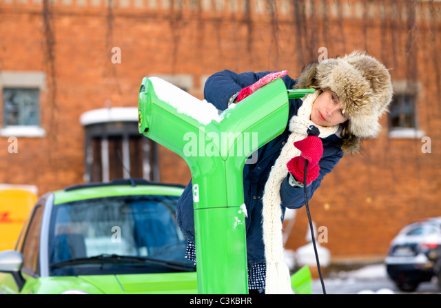 Young woman charging electric car - Stock Image