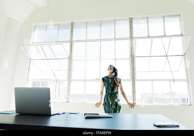 Businesswoman looking out of office window - Stock Image