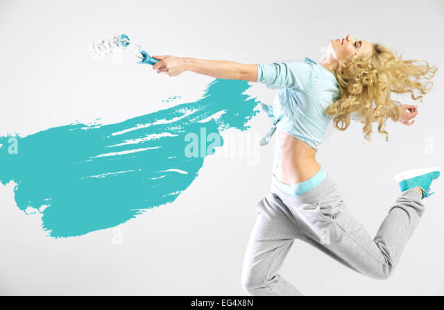 Fit lady painting empty walls - Stock Image