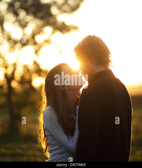 Loving couple kissing in backlight - Stock Image